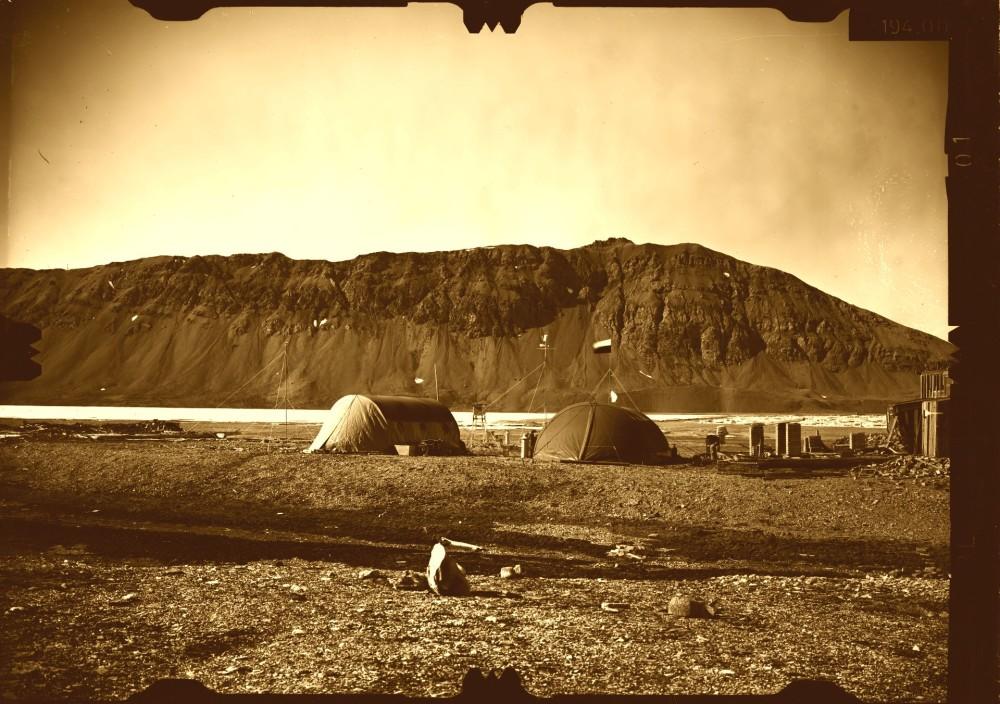 Baza pierwszej wyprawy Uniwersytetu Śląskiego na Spitsbergen w 1978r. Widoczne namioty, chata traperska oraz stacja meteorologiczna. Badawcze zdjęcie fotogrametryczne stoku masywu Wurmbrandegga – na drugim planie