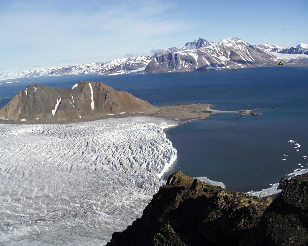Widok na fiord Hornsund z północy. Trójkątem zaznaczono lokalizację bazy wyprawy UŚ z 1978 r. Na pierwszym planie Lodowiec Hansa